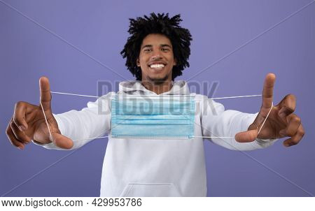Cool Black Teen Guy Holding Face Mask In Outstretched Hands, Happy About End Of Coronavirus Epidemic