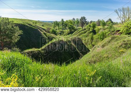 Gorge Between Hills With Steep Slopes And Precipitous Ravines, Overgrown With Grass And Single Trees