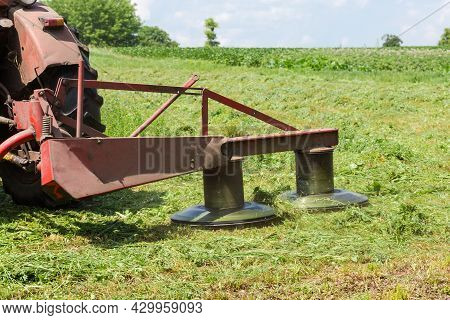 Tractor Mounted Rotary Mower During Mowing Of Hay On A Hayfield At Summer Day, Fragment Close-up