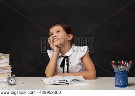 Happy Schoolgirl Daydreaming And Sitting At Table