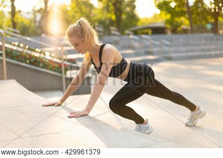 Sport And Fitness Fit Young Adult Woman Doing Plank Exercise Outdoor Urban Environment. Sunlight Sum