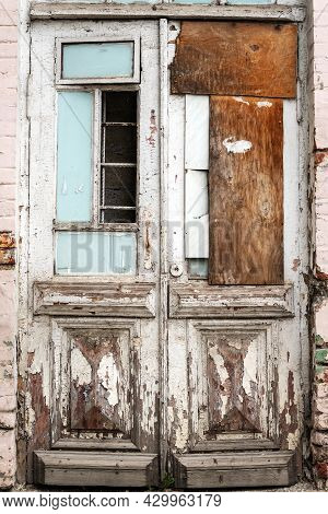Old Double-double Doors With No Part Of The Glass. Inside There Is A Metal Lattice And A Brick Wall