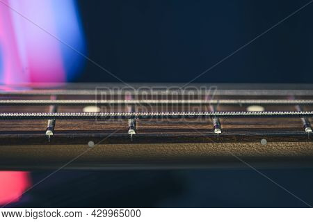 Close-up Of Strings On The Fretboard Of A Bass Guitar On A Blurred Dark Background.