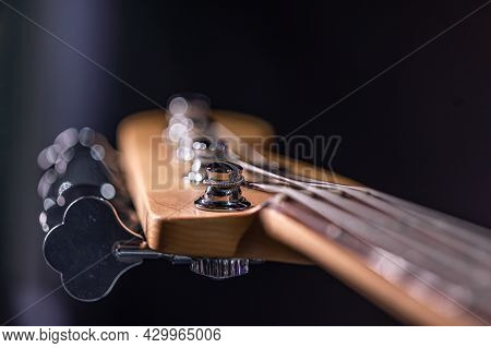 Detail Of A Tuning Post On The Wooden Headstock Of An Electric Bass Guitar.