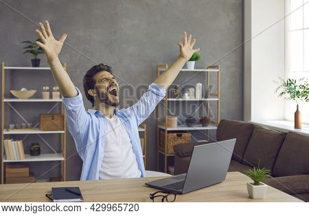 Happy Excited Young Man Screaming Sitting At His Working Desk With Laptop Computer