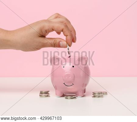 Female Hand Throws A Coin Into A Pink Piggy Bank On A White Table. Concept Of Accumulating Cash, Sav