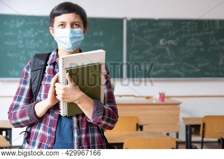 Smiling student girl wearing school backpack, mask and holding exercise book. Social distanting and classroom safety during coronavirus epidemic