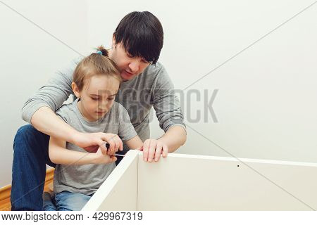 Father Teaching His Son To Assemble New Furniture. Do It Yourself Furniture Assembly. Dad And Son As