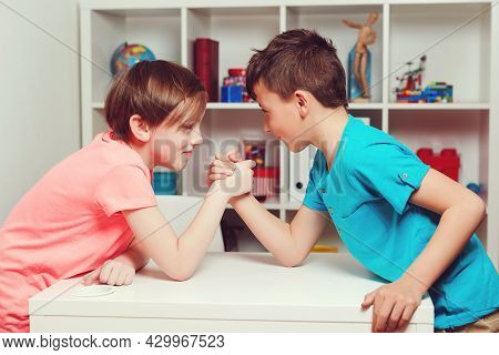 Classmates Competing In Arm Wrestling During The Break. Happy Friends Playing Arm Wrestle Looking At
