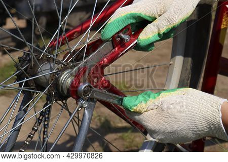 Men's Gloved Hands Repair The Back Wheel Of The Bike, Close-up. A Man Repairs A Vintage Bicycle Outd