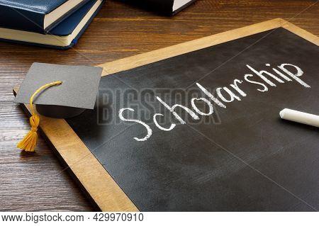 Scholarship Written On The Blackboard And Graduation Cap.