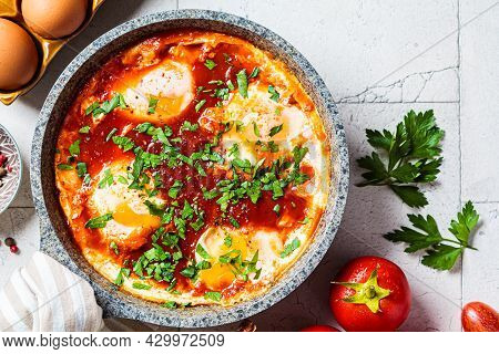 Traditional Israeli Shakshuka In A Gray Frying Pan. Fried Eggs In Tomato Sauce, Top View.