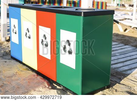 Close-up Photo Of Four Different Color Recycling Containers With Logos Standing On Summer Beach. Blu