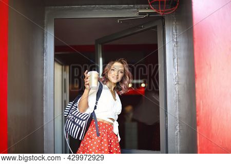 Portrait Of Happy Young Beautiful Woman With Curly Hair Holding Coffee Cup, Standing On City Street