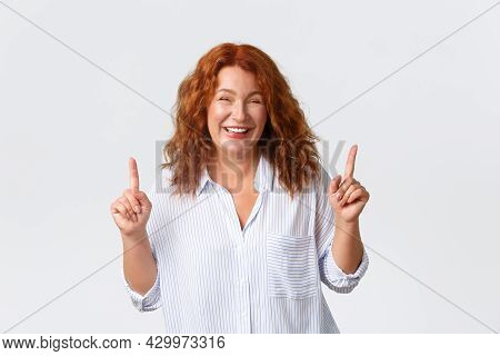 Cheerful Smiling And Carefree, Beautiful Middle-aged Woman With Red Hair, Pointing Fingers Up While