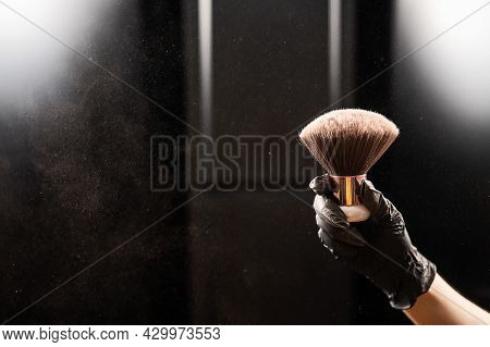 A Woman Shakes A Large Powder Brush With Clouds Of Dust On A Black Background. Treatment After Insta