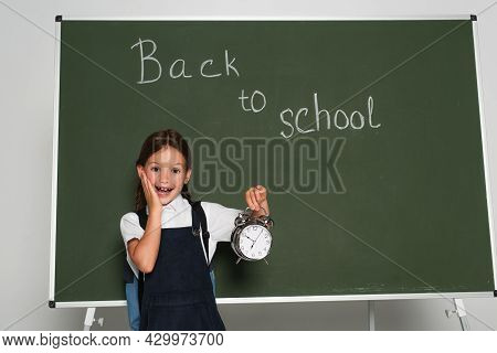 Amazed Schoolkid Holding Alarm Clock Near Chalkboard With Back To School Lettering On Grey