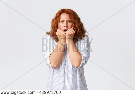 Scared And Horrified Caucasian Middle-aged Redhead Woman Holding Hands Pressed To Mouth, Shivering F