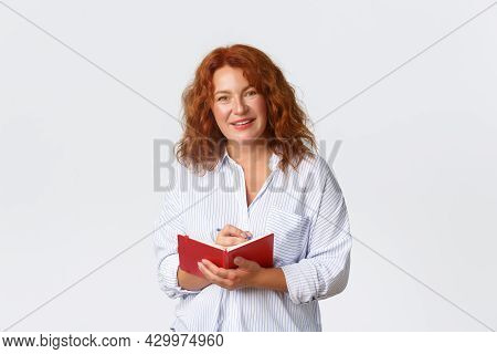 Portrait Of Pleasant And Smiling Redhead Middle-aged Therapist Or Teacher, Woman Taking Notes In Her