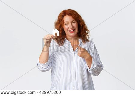 Rent, Buying Property And Real Estate Concept. Cheerful Middle-aged Redhead Woman Becomming Home Own