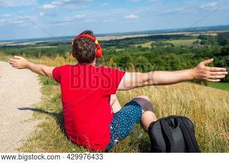 Young Male Person Arms Outstretched Enjoys Music In Headset From Cell Phone In Mountains. Man Sittin