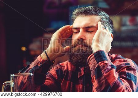 Alone Bearded Man Sitting At The Bar Counter. Alcohol Addiction. Stressed Man Drinking Beer At Pub.