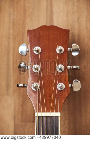 Front View Of A Guitar Headstock. Close-up Vertical Image With Wood Background.