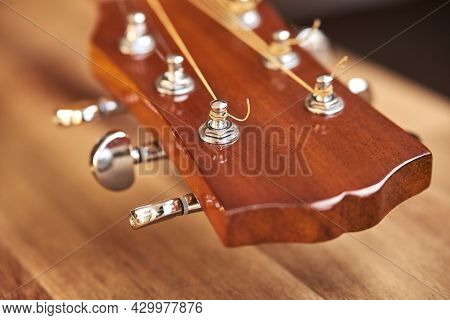 Guitar Headstock On A Wooden Surface. Close-up Horizontal Image With Selective Focus.