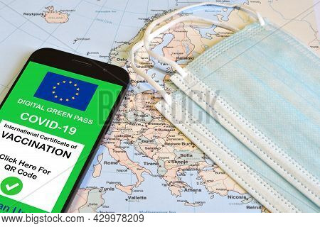 The Digital Green Pass Of The European Union On Smartphones Together With Surgical Masks On A Geogra