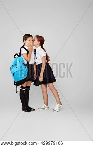 Two Happy Little Cheerful Friends Schoolgirls With Backpacks