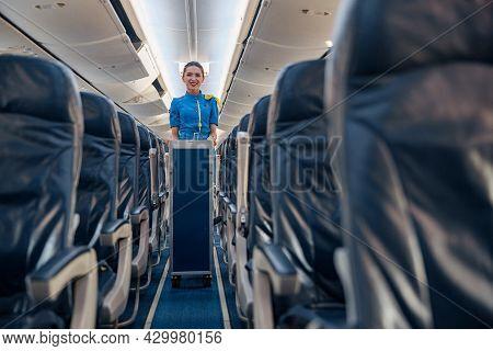 Female Cabin Attendant Leading Trolley Cart Through Empty Plane Aisle