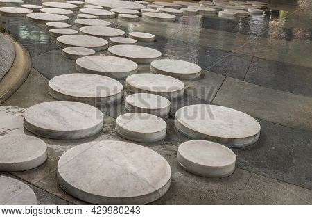 Sidewalk Paved With Round Stone, Rock Or Concrete Slabs Of Various Sizes For Landscape By Paving In