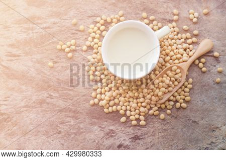 Top View Of Fresh Delicious Homemade Soybean Milk In Soft Yellow Cup With Dry Soybean Seeds On Grung