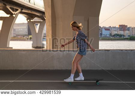 Active Casual Woman Skating Under Bridge. Blonde Female In Summer Street Style Clothes Riding Longbo