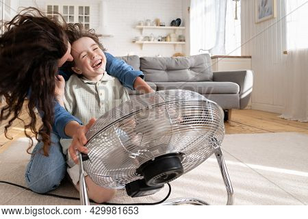 Playful Single Mother Bonding With Son Excited Playing Together At Home With Big Fan Blowing Cool Wi