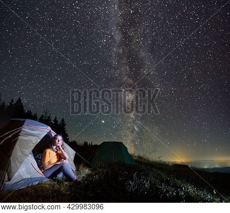 Fantastic View Of Night Starry Sky Over Grassy Hill With Camp Tents And Female Traveler. Charming Yo