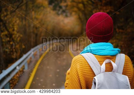 Beautiful Female Hipster In A Red Hat, Yellow Sweater And Blue Scarf Walks In The Autumn Nature. Coo