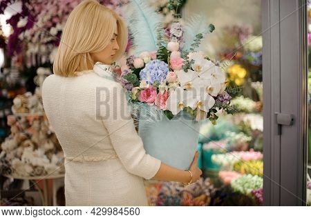 Rear View Of Woman With Blue Box With Flower Arrangement Of Orchids Hydrangea Decorated With Blue Fe