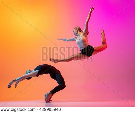 Two Dancers, Stylish Sportive Couple, Male And Female Models Dancing Contemporary Dance On Colorful