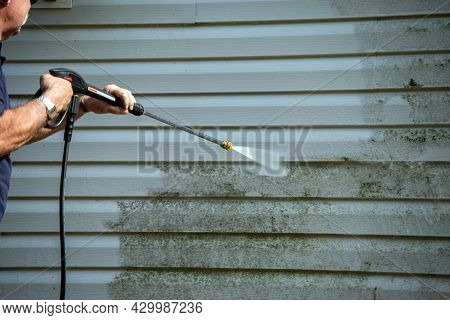 An Unidentified Man Uses A Power Washer To Clean Mold And Grime Off The Siding Of A House.