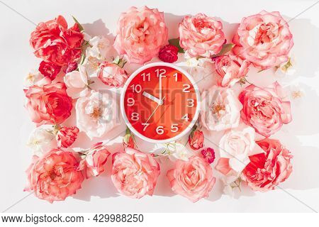 Round Analog Alarm Clock With Rose Buds On White Background. Summer Morning Concept. Top View. Flat