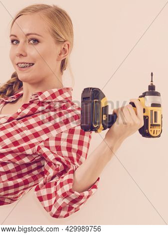 Woman Holding Yellow Driller About To Drill Something And Aiming. Hardware Construction Site Objects