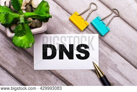 On A Wooden Background, A White Card With The Text Dns Domain Name System, Yellow And Green Paper Cl