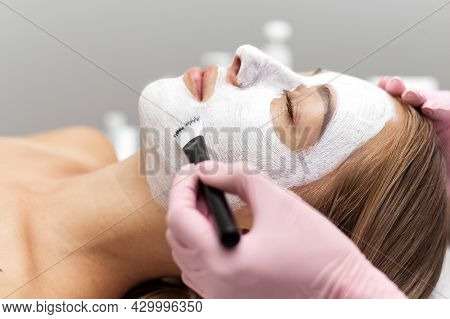 Beautician Applies A White Clay Face Mask With A Brush On A Womans Face. Professional Beautician App