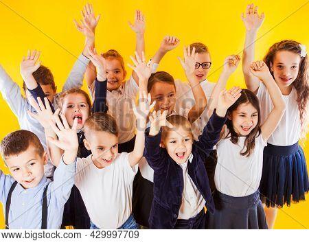 The Happy Schoolchildren In Uniform Raised Their Hands Up