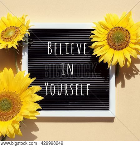 Believe In Yourself, Text On Letter Board With Sunflowers. Flat Lay With Natural Flowers And Motivat