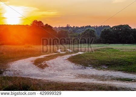 A Dirt Road At Sunset, Going Into The Forest On A Summer Evening. Summer Forest Landscape, Trees, Gr