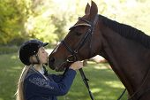 Female rider kissing horse, outdoor photo. Friendship between rider and horse. poster