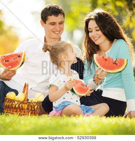 Happy family having a picnic in the autumn garden