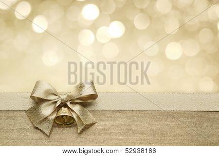 Laço de fita dourada com bokeh, decoração de Natal.